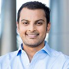 Closeup headshot portrait, happy handsome business man, smiling, in blue shirt,confident and friendly on isolated office interior background. Corporate success
